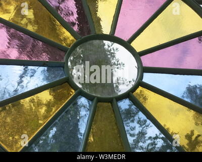 Circular leaded stained glass window with pink, yellow and blue coloured glass in the segments round a clear glass centre - Stock Photo