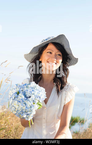 Beautiful, happy, healthy, smiling, young Asian woman holding fresh flowers outdoors in summer. She is wearing a feminine dress and sun hat. Natural h - Stock Photo