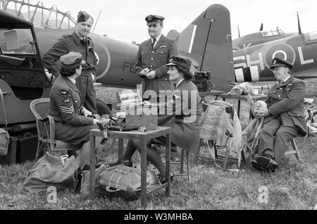 Battle of Britain era Second World War scenario with pilots, WRAFs & ground crew engineer re-enactors in discussion. Planes. Monochrome. Black & white - Stock Photo