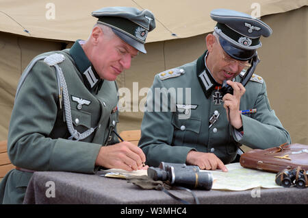Second World War re-enactors depicted German Army officer soldiers planning with maps and communicating via telephone. Wehrmacht, Heer. - Stock Photo
