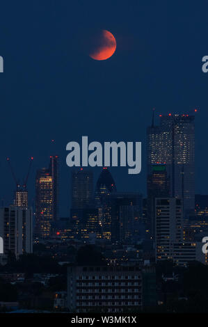 London, UK. 16th July, 2019. UK Weather: The 'Buck Moon' full moon rising over London. A partial lunar eclipse seen from Parliament Hill in Hampstead Heath. Credit: Marcin Rogozinski/Alamy Live News - Stock Photo