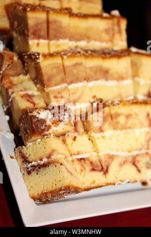 Fresh baked marble cake cut into finger sized pieces with icing on a serving plate - Stock Photo