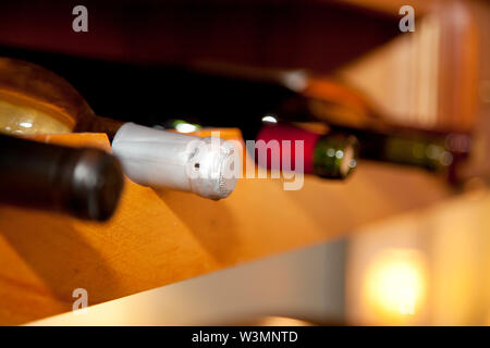 The necks of four different types of wine in a row in a collection or wine cellar - Stock Photo