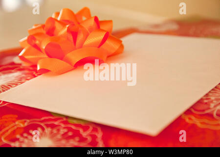 Red wrapping paper on a box with an orange bow and an envelope with copy space - Stock Photo
