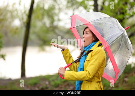 Woman walking in the rain in Autumn forest. Pretty girl feels the raindrops walking in forest by lake in fall. Mixed race Asian Caucasian female model with funny ecxpression.