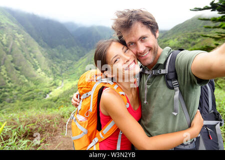 Hiking couple - Active young couple in love. Couple taking self-portrait picture on hike. Man and woman hiker trekking on Waihee ridge trail Maui USA. Happy romantic interracial couple.