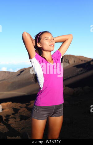 Athlete runner woman relaxing after running. Fitness girl resting after training outside in beautiful nature landscape. Fit sport fitness model outdoors at sunset. Multi-ethnic Asian Caucasian female.