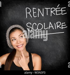 Rentree Scolaire - French college university student woman thinking Back to School written in French on blackboard by female on green chalkboard. French language at college or high school. - Stock Photo