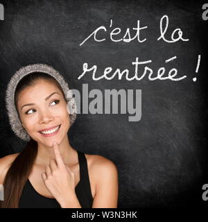Cest la Rentree Scolaire - French college university student woman thinking Back to School written in French on blackboard by female on chalkboard. French language at college or high school. - Stock Photo