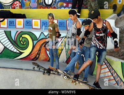 (190717) -- DAMASCUS, July 17, 2019 (Xinhua) -- Boys skateboard during the opening of the first skatepark in Damascus, Syria, July 15, 2019. The skatepark was co-built by SOS Children's Villages in Syria, the German Skate Aid Foundation and Wonders Around the World, an international and independent non-profit organization. The park, which was officially opened on Monday, was completed in 26 days in an abandoned space close to a residential area that witnessed some acts of rebellion in the early years of the eight-year war in Syria. TO GO WITH 'Feature: First skatepark adds new dimension to Syr - Stock Photo