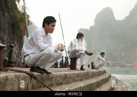 3 sailors who work as crew members on vacation tourist boats wait at dock with the lime stone towers of Ha Long Bay behind them - Stock Photo