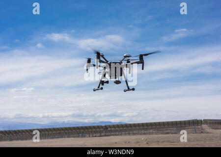 Drone flying and working for ortophoto thermal analysis of PV Plants with visual and thermal camera. UAV are used for solar energy aerial inspections - Stock Photo