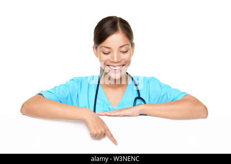 Beautiful young female doctor pointing at copyspace over white background - Stock Photo