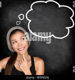 Thinking student hipster woman by blackboard with thought bubble speech balloon. Multiracial hipster university college student pensive and contemplating looking at chalkboard black background. - Stock Photo