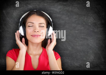 Music in headphones. Beautiful young Asian woman with her eyes closed in bliss listening to music wearing a set of headphones and standing against black blackboard background with copyspace - Stock Photo