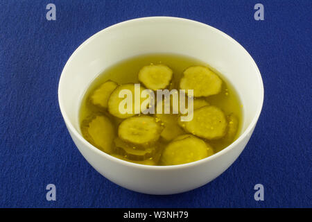 Sweet southern bread and butter pickles in pickle juice in white bowl on blue background - Stock Photo