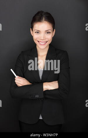 Teacher woman with chalk smiling happy portrait. Beautiful young female teacher holding chalk by blackboard. Teacher or business woman before lecture. Multiracial Asian Caucasian female model on black - Stock Photo