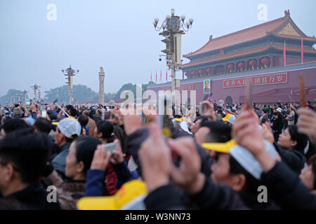 lots of people with cameras and cellphone outside of the forbidden city in beijing - Stock Photo