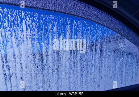 Looking out through a car window that is being washed at the car wash - Stock Photo