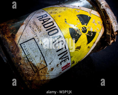 Radiation warning sign on transport index label stick on the rust and decay radioactive material container - Stock Photo