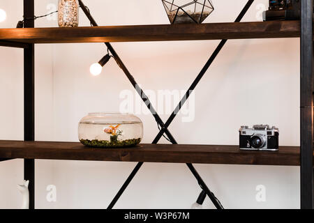 Photo of Wooden shelf in the room with an aquarium and decor - Stock Photo