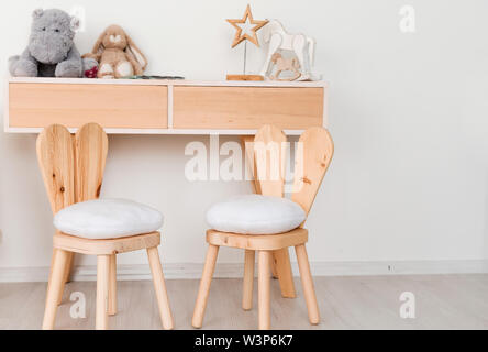 2 chairs with bunny ears in the children's room and a table with toys - Stock Photo