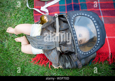 Baby's gas mask from the second world war, UK with a doll in it - Stock Photo