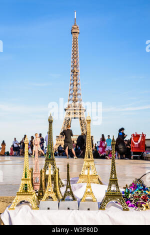 The Eiffel tower in Paris, France, pictured with miniature Eiffel towers in the foreground, sold on the Trocadero esplanade by street vendors. - Stock Photo