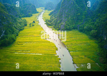 Aerial image of Tam Coc at harvest time where tourists can cruise along a stream with nice paddy fields alongside. - Stock Photo