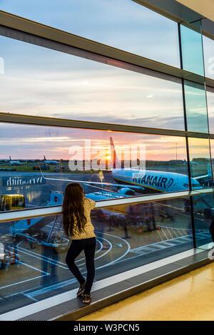 Dublin Airport, Terminal One, child, girl watches sunrise. Ireland - Stock Photo