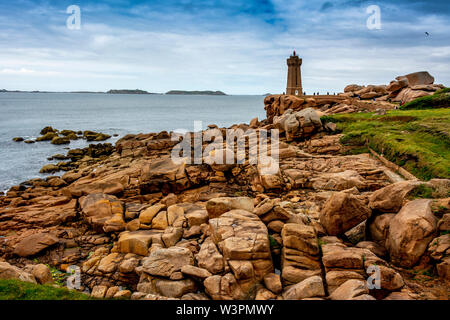 Ploumanach Mean Ruz lighthouse red sunset in pink granite coast, Perros Guirec, Cotes d'Armor, France - Stock Photo