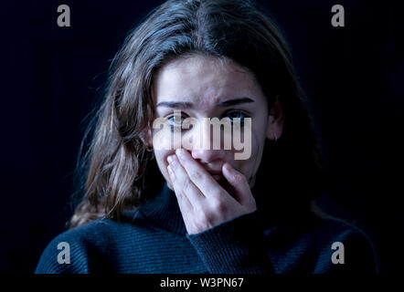 Dramatic closeup portrait of young scared, depressed girl crying alone, feeling hopeless suffering from harassment or domestic violence. Stop child ab