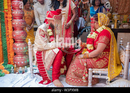 A bride and groom exchange rings during a traditional Hindu wedding ceremony in a temple in Ozone Park, Queens, New York City. - Stock Photo