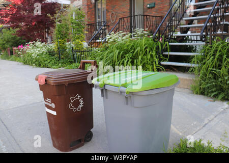 Brown Compost and Recycling Bins on a sidewalk during collection day in Montreal, Rosemont, Quebec, Canada - Stock Photo