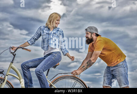 Support and friendship. Woman rides bicycle sky background. Service and assistance. Man helps keep balance ride bike. Girl cycling while man support her. Support helps believe in yourself. - Stock Photo