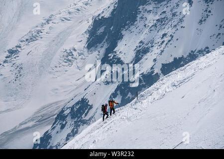 Chamonix, France - 18/06/2019: Mountaineers ascending towards Aiguille du Midi on a snowy ridge. - Stock Photo
