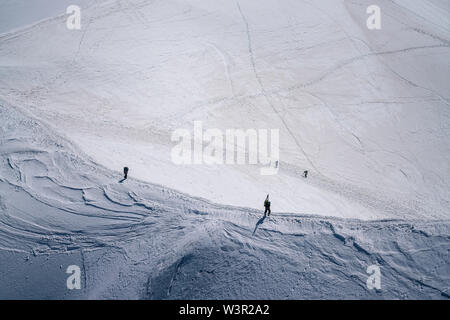 Alpinists and skiers ascending on a ridge towards Aiguille Du Midi in Chamonix, France - Stock Photo