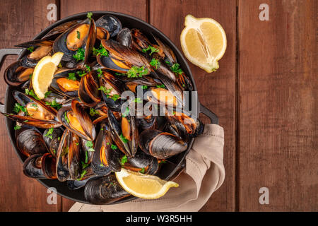 Marinara mussels, moules mariniere, with lemon slices, in a cooking pot, shot from the top on a dark rustic wooden background with copy space - Stock Photo