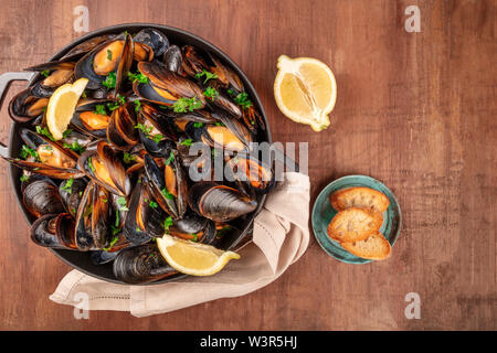 Marinara mussels, moules mariniere, with toasted bread and lemon slices, in a cooking pot, overhead shot on a dark rustic wooden background - Stock Photo