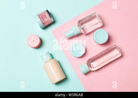 Top view of different cosmetic bottles and container for cosmetics on pink and blue background. Flat lay composition with copy space. - Stock Photo