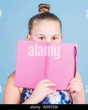 learn reading books. secret story. workbooks for writing. school diaries for making notes. small girl with note book. school child with notepad. education concept. detective story. reading a novel. - Stock Photo