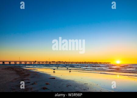 People walking on Semaphore beach jetty at sunset - Stock Photo