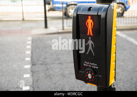 Traffic light control with red man illuminated at pedestrian crossing in a city centre - Stock Photo