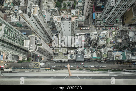 Person smoking from balcony in High-rise building in Hong Kong - Stock Photo