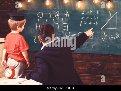 Young male teacher guides his child student to learning while pointing and looking at chalkboard with scribbles on, sitting in classroom, rear view. - Stock Photo