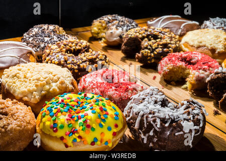 assorted donuts, some with bites missing, on wooden cutting board reflected in mirror - Stock Photo