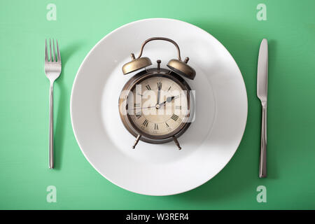 concept of intermittent fasting, ketogenic diet, weight loss. alarmclock on a plate