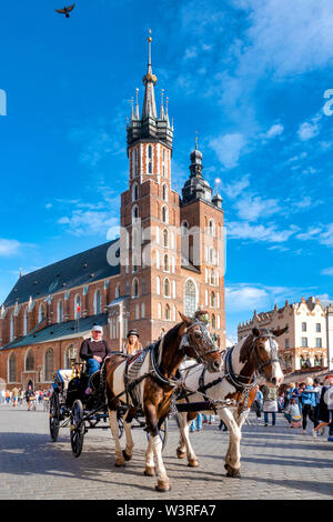 Horse drawn carriage in the Main Market Square, Krakow, Poland - Stock Photo
