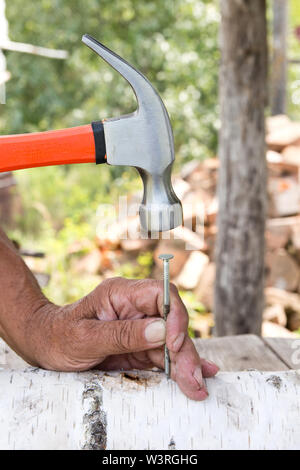 To hammer a nail with a hammer. Older worker carpenter - Stock Photo
