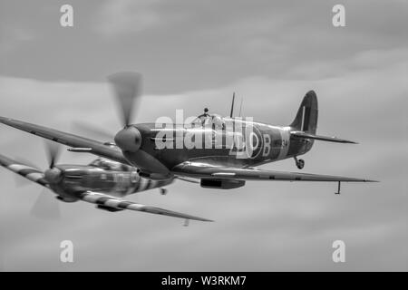 Vickers-Supermarine Spitfire LFIXb G-ASJV MH434/ZD-B world war 2 fighter aircraft in flight, panned with motion blur on the propeller blades. - Stock Photo